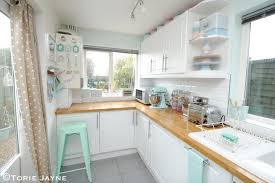 pastel kitchen ideas wooden countertop white cabinets pastel mint green chair and towel