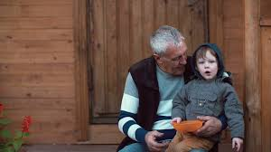 grandfather s grandson sitting on grandfather s lap and pointing with his finger