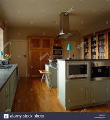 kitchen island extractor fan microwave and oven in island unit in modern kitchen with chrome