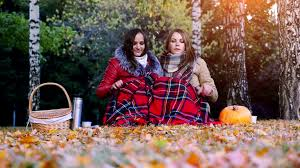 young women sitting on picnic bundled up in a blanket drinking