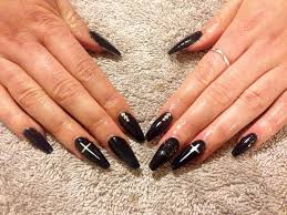 my first set of gel nails black coffin shape with white cross and