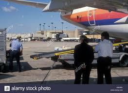 united baggage united air lines supervisors watch baggage handler unload jet at