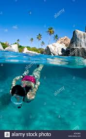 female snorkeler split view at baths beach in bvi british virgin