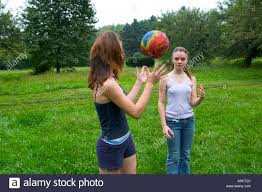 teen sisters playing with a ball in their backyard model released