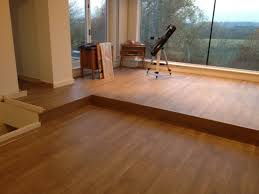 wooden laminate flooring in living room design with glass curtain