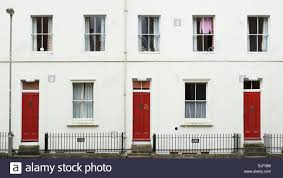 three terrace town houses with red front doors museum road
