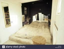 sheepskin rug on bed with mirrored headboard in sixties bedroom