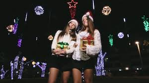 two lovely twin sisters dancing in the mood of christmas holding