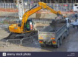 jcb excavator digger loading a tipper lorry with earth from