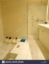 white tiled bathroom with shower and sunken bath stock photo