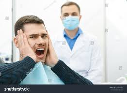 young male patient looking terrified visiting stock photo