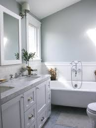 a white bathtub backsplash tile mirror and window frame contrast
