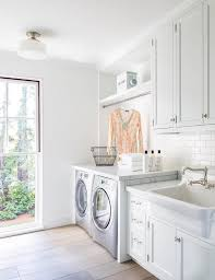 Apron Sink With Backsplash by White Laundry Room Features White Cabinets Adorned With Vintage