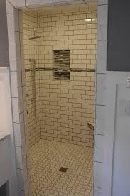 white subway tile shower with glass inserts after bathroom