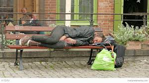 homeless man sleeps on a bench in the city stock video footage
