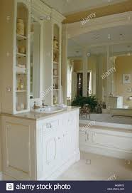 basin in fitted vanity unit in bathroom with large mirror above