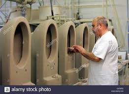 an employee of the duravit ag works on still moist toilet seats in