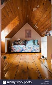 small attic bedroom with blue and pink floral pattern folding bed