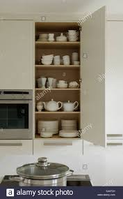 open shelving in kitchen with oven and extractor fan stock photo open crockery cupboard in white contemporary kitchen stock photo