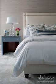 ivory nailhead bed with blue nightstand and gray walls