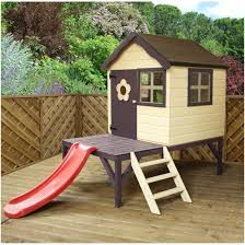 outdoor wooden playhouse kidsized wicker furniture in front of