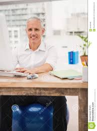 Sitting On A Medicine Ball At Desk Smiling Casual Businessman Sitting On Exercise Ball At Desk Stock