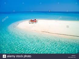 Chairs On A Beach Two Women Relaxing In Solitude On Beach Chairs On Sandbar In