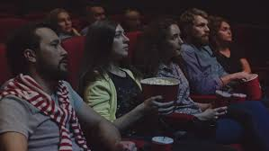 young people watch movies in cinema horror in 3d all smiling and