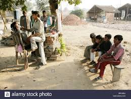 schoolboys waiting for a haircut at a roadside barbers near agra