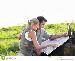 jeep couple couple looking at map on jeep bonnet at landscape stock image