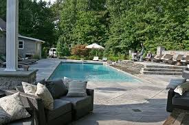 Luxury Pool Design - outdoors luxury pool with concrete poil deck and black wicker