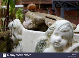 weathered and faded garden ornament next to broken solar light