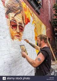 artist painting a street art mural on a wall in williamsburg stock artist painting a street art mural on a wall in williamsburg brooklyn nyc