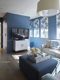 blue cottage living room with light gray sofa and blue ottoman