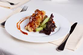 Chicken Main Dish - fried chicken main dish with sauce on vegetables stock photo