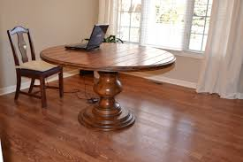 round glass top dining table with curvy dark brown wooden base
