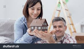 Their Home by Happy Smiling Couple Holding Model House Stock Photo 551805322