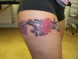 flowers garter tattoo on upper thigh