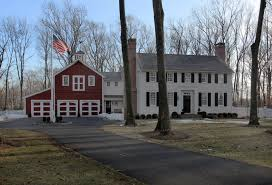 red barn garage with white colonial house lottery win