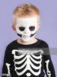 portrait of boy in skeleton costume for halloween stock photo