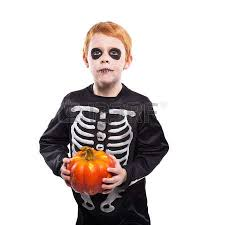 surprised red hair boy in halloween costume holding a orange