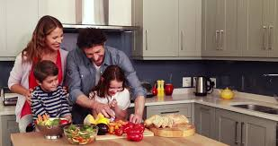 happy family preparing vegetables together in the kitchen stock