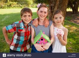 children holding birdhouse in backyard stock photo royalty free