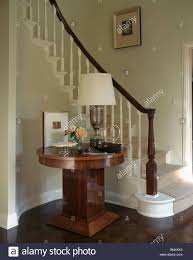 lamp on circular antique table beside curved staircase in