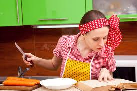 femme dans la cuisine femme dans la cuisine avec le livre de recette de couteau photo