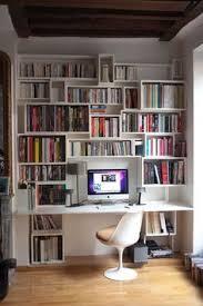 bibliothèque avec bureau intégré bureau à l étage avec bibliothèque suit l escalier avec la fenêtre d