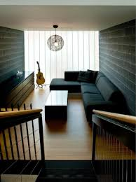 black sofa color with black brick wall and wooden floor for narrow