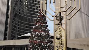 outdoor hanukkah menorah evening at toronto city with a christmas tree and menorah