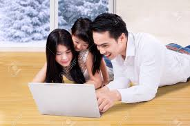 Asian Wooden Floor Happy Asian Family Using A Laptop Computer While Lying Down On
