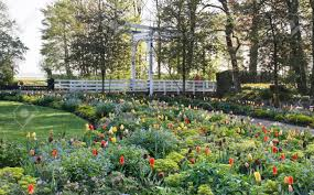 A Garden Of Flowers by Garden In Spring With Lots Of Flowers And White Lifting Bridge